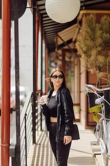 見事なブルネットの少女のアウトドアライフスタイルの肖像画。コーヒーを飲み、街の通りを歩きます。