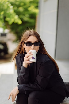Outdoors lifestyle portrait of stunning brunette girl. drinking coffee and walking on the city street.