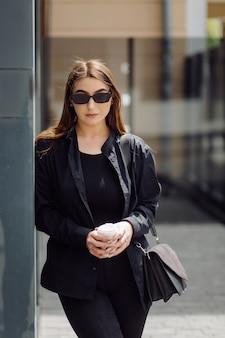 Ritratto di stile di vita all'aperto di splendida ragazza bruna. bere caffè e camminare per le strade della città.
