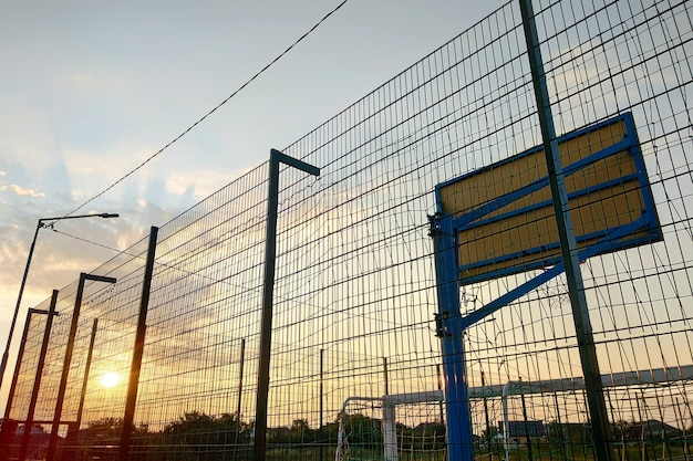 Outdoors mini football and basketball court with ball gate and basket surrounded with high protective fence.