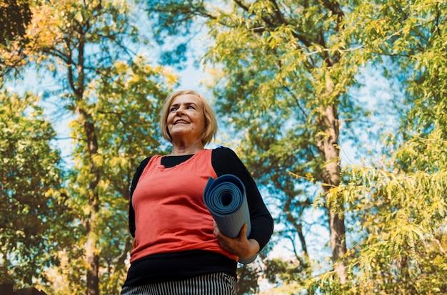 Старая старшая женщина с циновкой йоги outdoors в древесинах идя на тренировку. здоровый образ жизни и тренировка в выходе на пенсию. серые волосы созрели женскую разминку outdoors