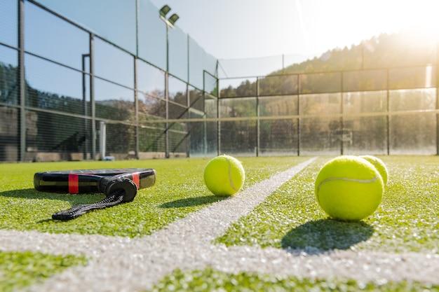 라켓과 공이있는 야외 패들 테니스 코트