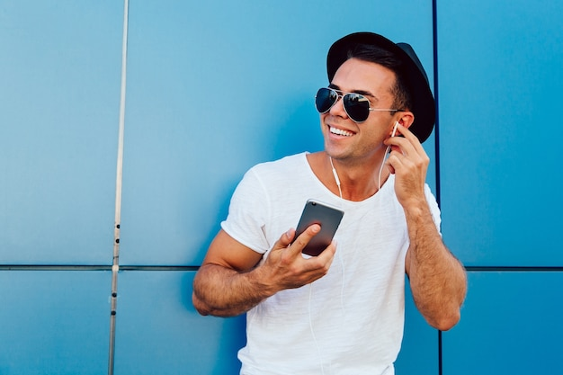 Outdoors photo of attractive guy in sunglasses listening to music in earphones