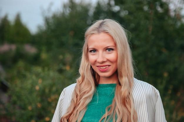 На открытом воздухе портрет взрослая женщина на природе, идущей в летнем лесу сумерек. мечтательница в одежде гуляет вечером по парковой зоне. положительные эмоции женщины в парке на рассвете