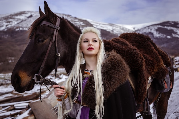 Outdoors portrait of beautiful furious scandinavian warrior ginger woman in  clothes with fur collar