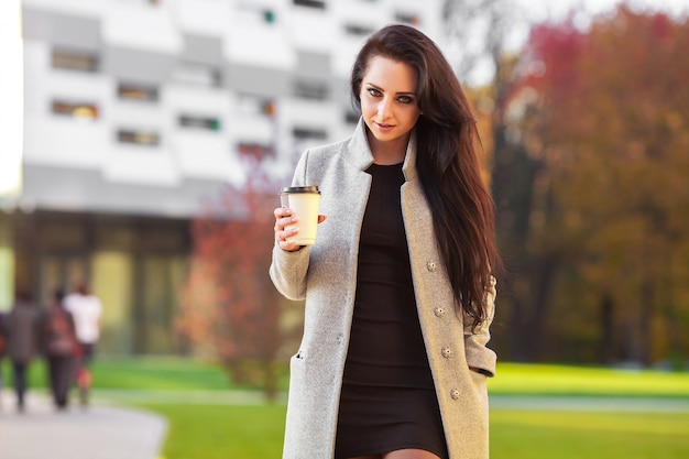 Outdoors portrait of cheerful beautiful brunette woman expresses happy emotions.
