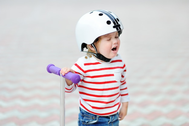 Outdoors portrait of crying toddler boy in safety helmet with scooter
