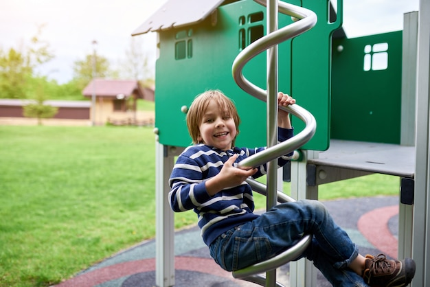 Outdoors portrait of cute preschool boy climbing at the playground