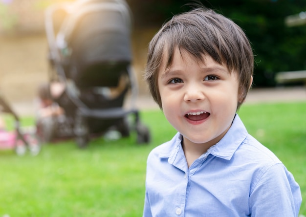 Outdoors portrait of happy boy with smiling face, kid having fun outdoors party with friends in summer, close up happy child face with blurry kids party