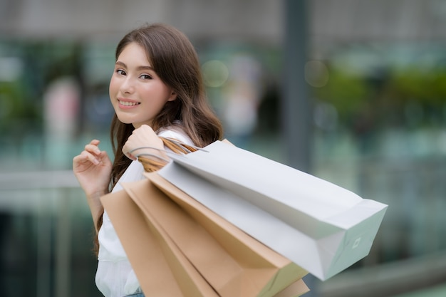 Outdoors portrait of happy woman holding shopping bags and smiling face at the mall