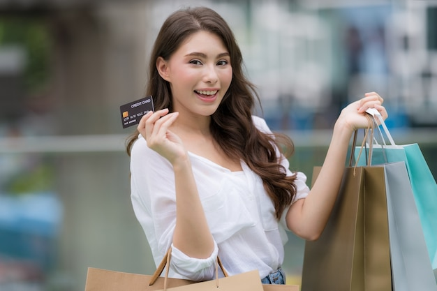 Outdoors portrait of happy woman holding shopping bags with credit card and smiling face at the mall