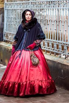На открытом воздухе портрет молодой викторианской женщины, идущей по старому городу