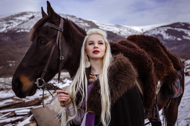 毛皮の襟付きの服を着た美しい猛烈なスカンジナビアの戦士生姜の女性の屋外の肖像画