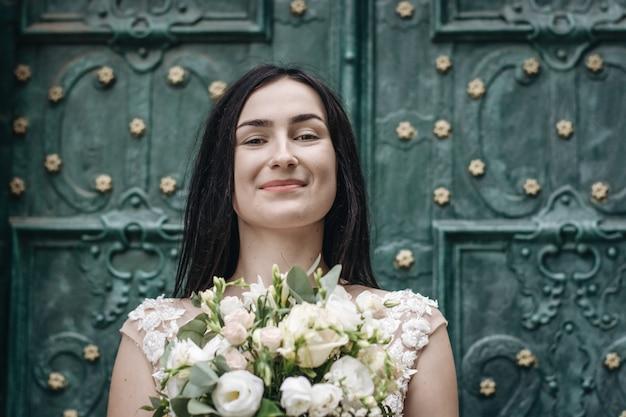배경에 오래 된 문을 통해 하얀 웨딩 드레스에 아름 다운 젊은 신부의 야외 초상화