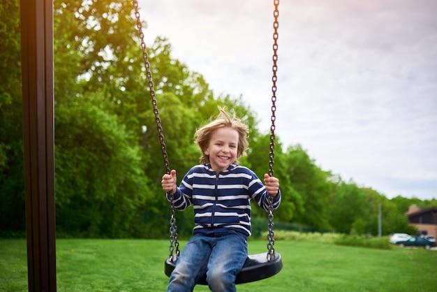 Портрет на свежем воздухе милый смех мальчика дошкольного качается на качелях на детской площадке