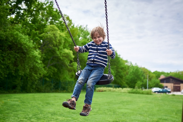 遊び場でブランコに揺れてかわいい就学前笑っている少年の屋外ポートレート