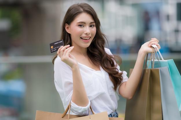 Портрет на открытом воздухе счастливой женщины, держащей хозяйственные сумки с кредитной картой и улыбающимся лицом в торговом центре