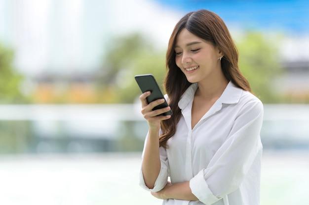 街で電話を使用して幸せな若い女性の屋外の肖像画