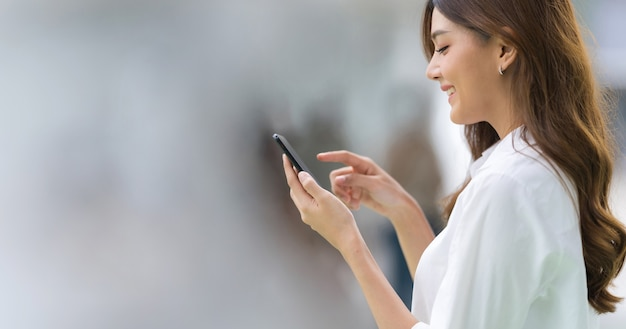도시에서 전화를 사용하여 행복 한 젊은 여자의 야외 초상화