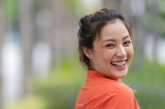 Портрет на открытом воздухе счастливой молодой женщины с улыбающимся лицом