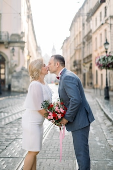 旧市街のロマンチックなカップルの屋外の肖像画。青いスーツを着たハンサムな成熟した男は、ドレスを着て、キスをし、手をつないで彼の見事なきれいな金髪の女性の妻と散歩を楽しんでいます