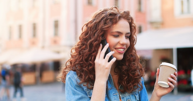 Портрет молодой стильной женщины в модной одежде на открытом воздухе, ярко улыбающейся и болтающей в ...