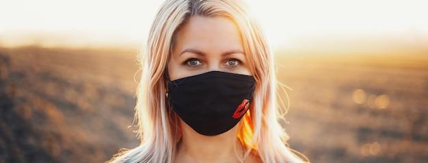 コロナウイルスとcovid-19に対する呼吸フェイスマスクを身に着けている女性の屋外の肖像画。