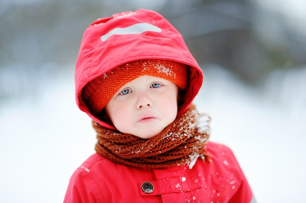 Outdoors portrait of sad crying little boy in winter. unhappy lonely child