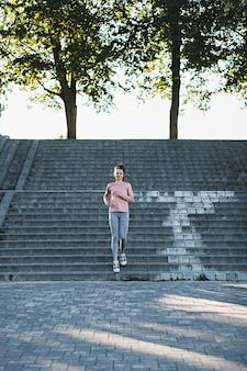 階段で走っている屋外の肖像画のスポーティな女性