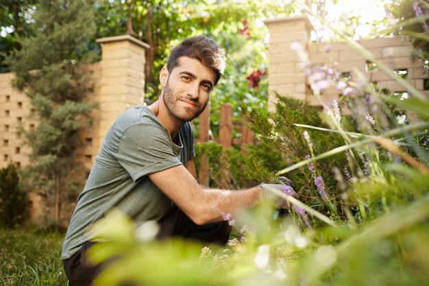 Outdoors portrait of young attractive bearded caucasian man in blue -shirt and sport pants smiling, sitting on grass, looking in camera with happy face expression, working in garden.