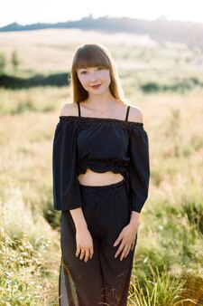 Outdoors portrait of young attractive girl in fashionable black suit, enjoying nature, posing to camera in beautiful green summer field in sunny day