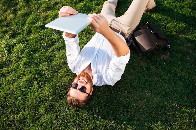 Взгляд сверху счастливого бородатого человека в солнечных очках и деловой одежде лежа на траве outdoors и делая selfie на планшете