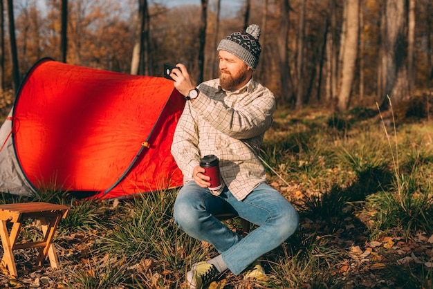 Outdoors shot of bearded man making photo in forest with his smart phone
