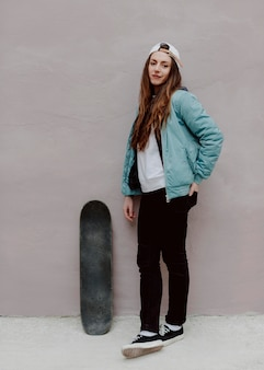 Ragazza pattinatrice all'aperto e il suo skateboard