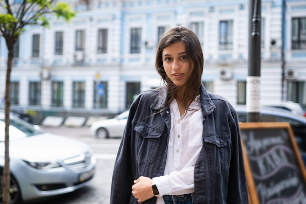 Outdoors street portrait of beautiful young brunette woman