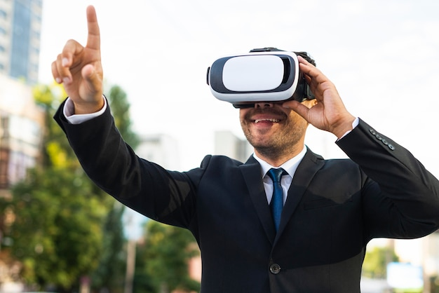 На открытом воздухе успешный деловой человек, использующий набор виртуальной реальности