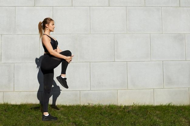 Ritratto di estate all'aperto di giovane donna attraente in abbigliamento sportivo che allunga il quadricipite, in piedi sull'erba contro il fondo del muro bianco con lo spazio della copia per il testo o il contenuto pubblicitario