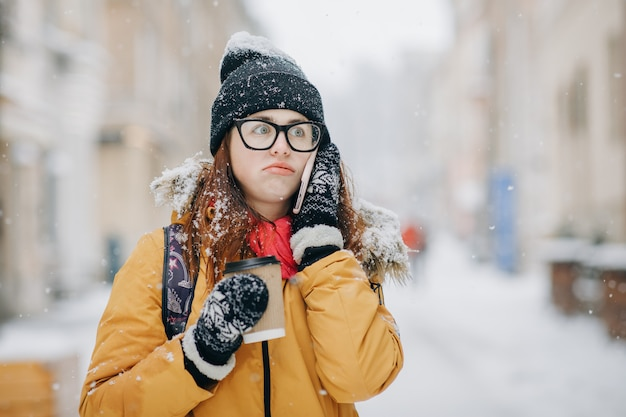 Outdoors winter portrait of beautiful teenage girl speaking on the phone