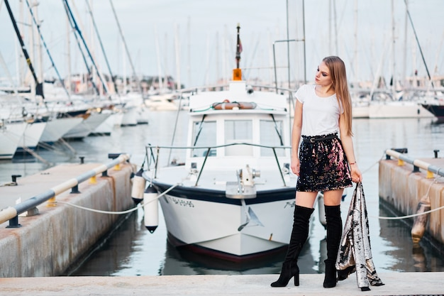Молодая привлекательная белокурая женщина представляя outdoors