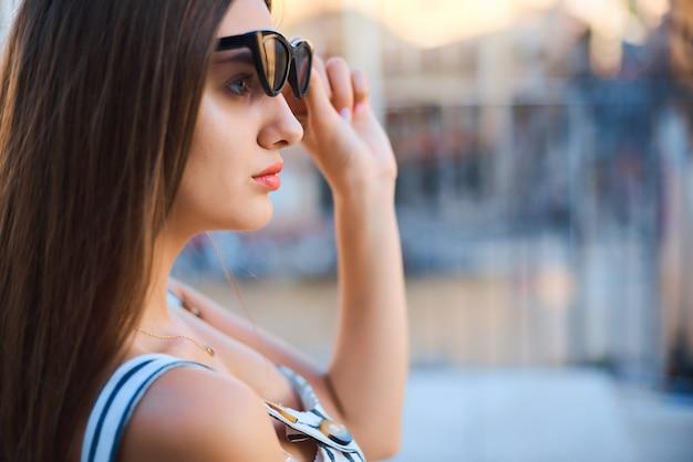 Фасонируйте портрет молодой женщины сидя и смотря в расстояние outdoors.