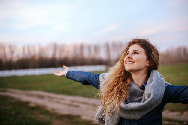 Портрет взгляда со стороны услаженной женщины стоя outdoors с ее поднятыми руками.