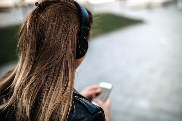 Вид сзади музыки девушки слушая на наушниках outdoors.