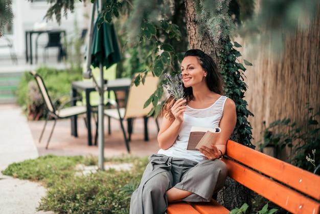 Наслаждаясь выходными. шикарная молодая женщина читая книгу и пахнуть цветки outdoors.