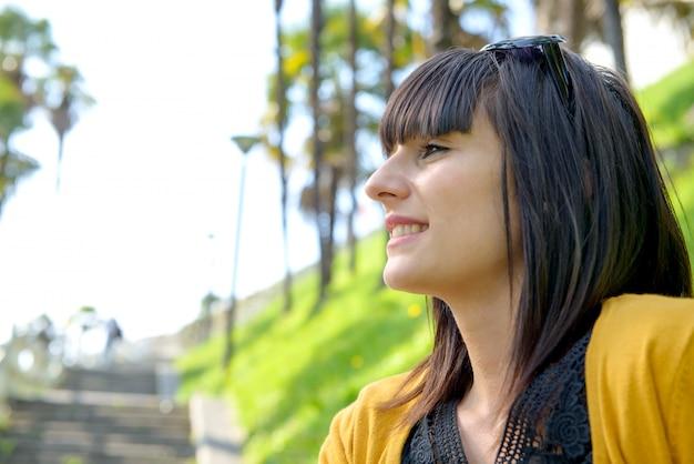 Молодая усмехаясь девушка брюнет, outdoors