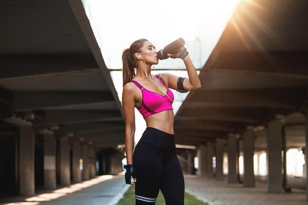 Красивый женский бегун стоя outdoors питьевая вода от ее бутылки.
