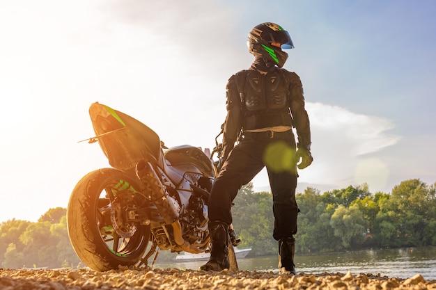 Укомплектуйте личным составом нося шлем мотоцикла и форму безопасности сидя на велосипеде outdoors, красивый сценарный ландшафт