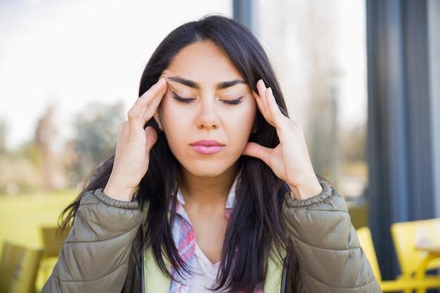 Утомленная женщина касаясь вискам outdoors