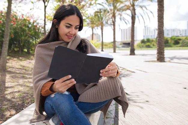 Усмехаясь милая женщина читая тетрадь с прописями и изучая outdoors