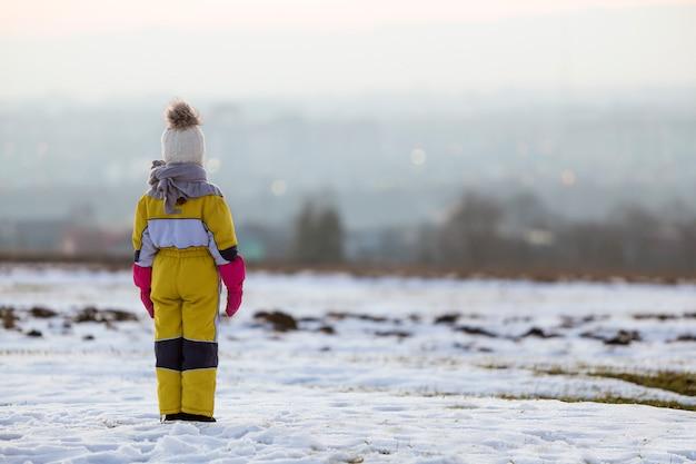Девушка маленького ребенка стоя outdoors самостоятельно на снеге покрыла поле зимы.