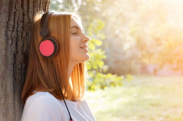 Портрет красного с волосами девочка-подростка слушая к музыке в больших розовых наушниках outdoors полагаясь к дереву.